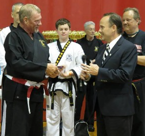 Grandmaster John Barton receiving a Lifetime Achievement award from PKC 4 PA State Director Master Grant Miller. In the background, from left to right, starting behind Grandmaster Barton are Mr. Heinselman, Chris Vottilla Master Ruvelo, and Master Bill LaVoice